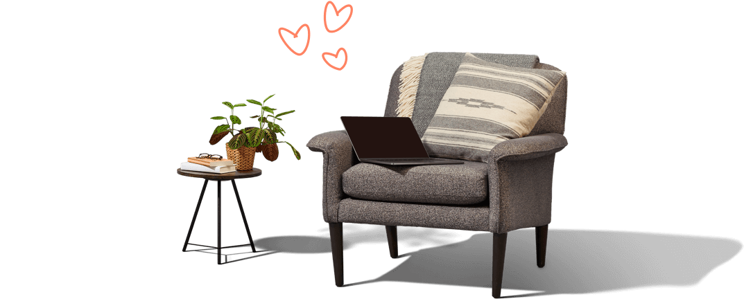 An armchair with blanket, cushion and laptop. A small side                     table with book, plant and glasses on it. The image includes                     Urban Jungle hearts above the chair.
