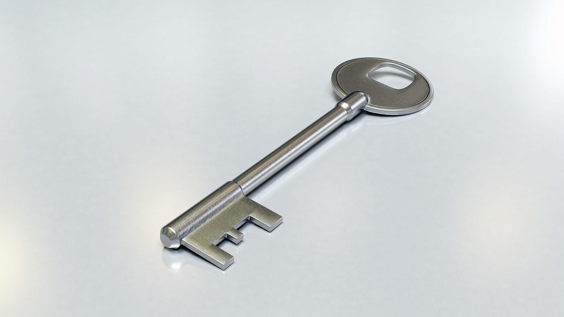 Silver deadlock key on white table