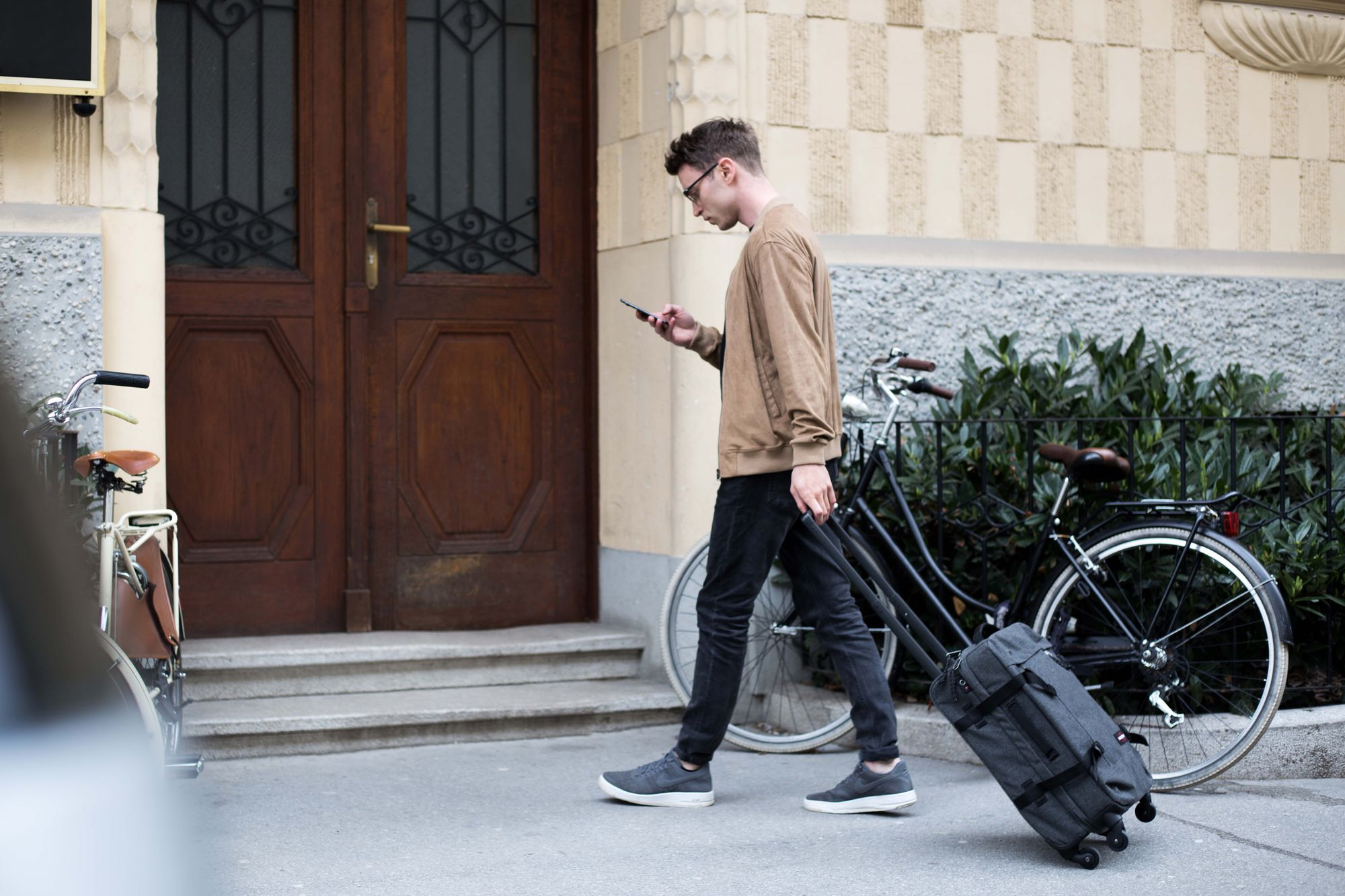 Man-outside-apartment-with-suitcase