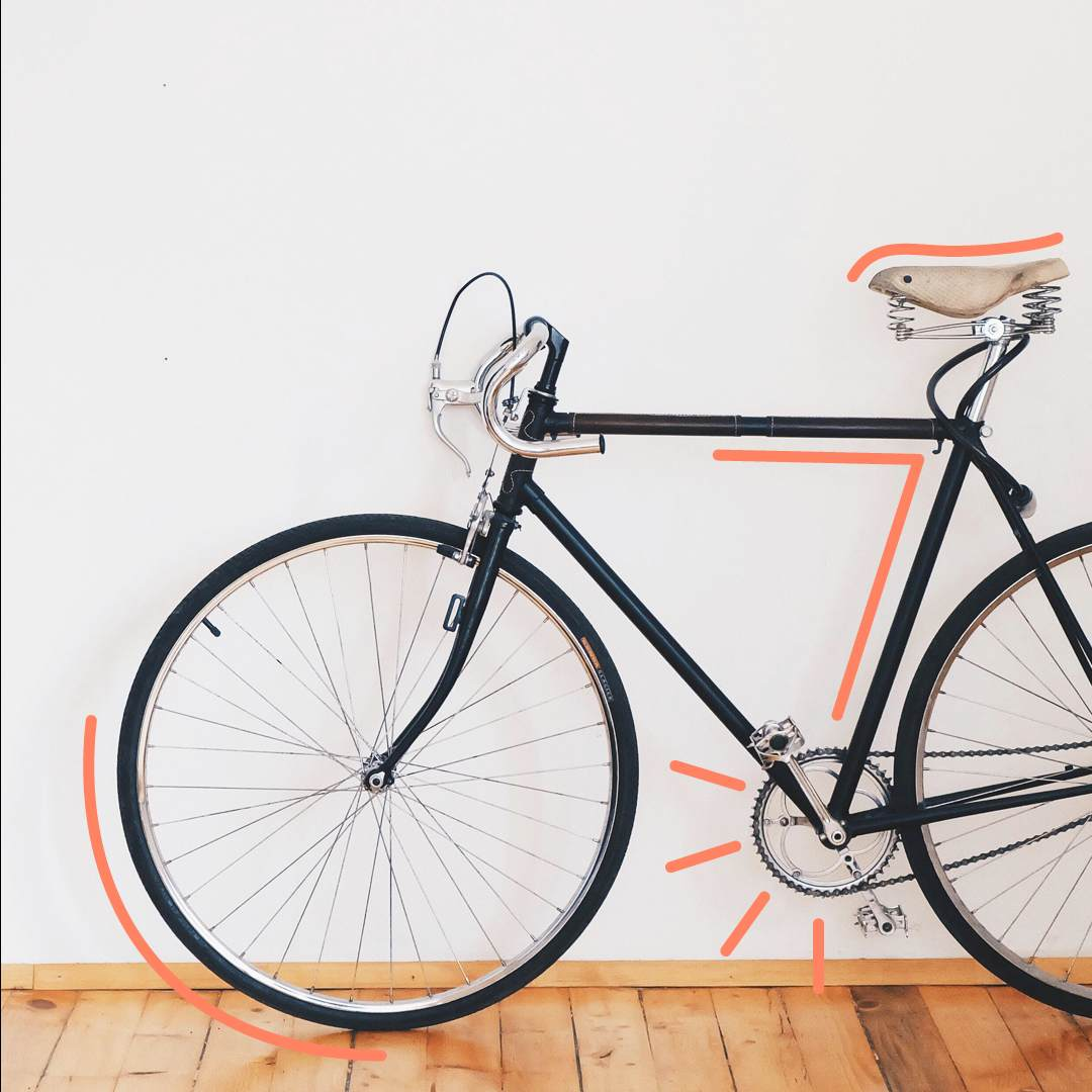 Bike-With-A-Black-Frame-In-Front-Of-A-White-Wall-With-Orange-Outline