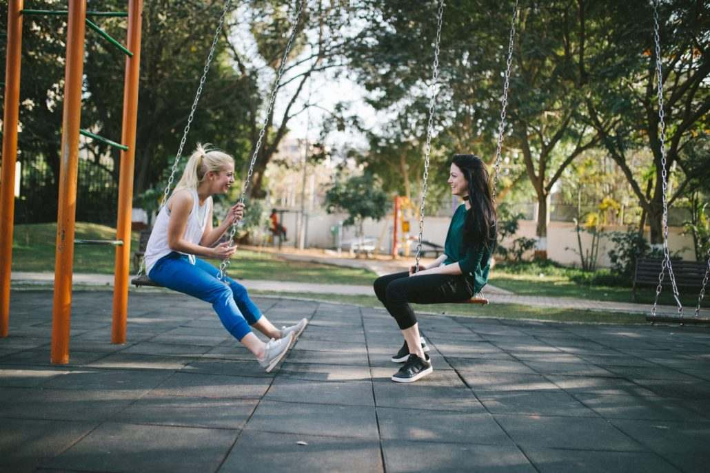 Two-Women-Laughing-On-Swings-In-The-Sun